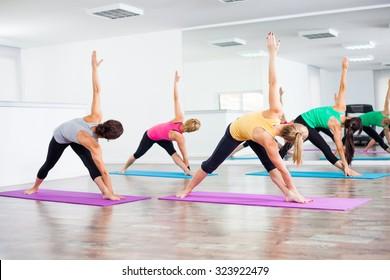 Four girls practicing yoga, Trikonasana Bikram/Bikram triangle right