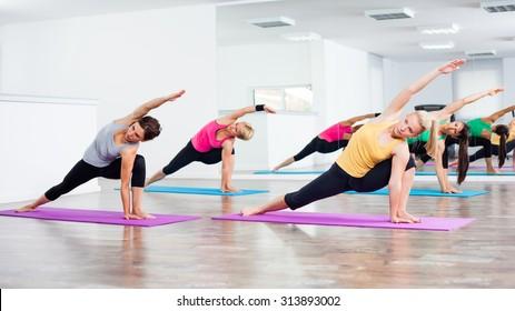 Four girls practicing yoga, Vasisthasana/Half side plank pose