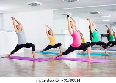 Four girls practicing yoga, Yoga - Virabhadrasana/Warrior pose