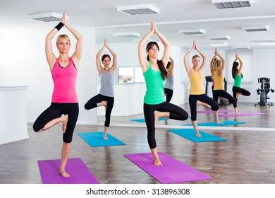 Four girls practicing yoga, Yoga - Vrikshasana / Tree pose