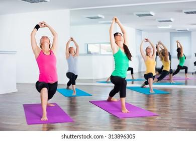 Four girls practicing yoga, Yoga-Virabhadrasana/Warrior pose