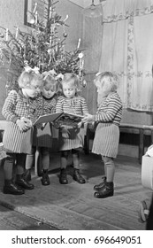 Four girls reading book by Christmas tree