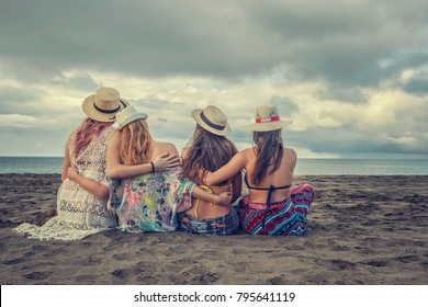 Four girls are sitting on the beach from behind and hugging each other like best friends forever in one summer day with view to the ocean. Photo has nice friendly and love emotion.