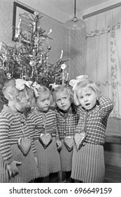 Four girls standing by Christmas tree