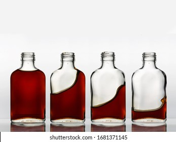 Four glass bottles in a row with different amount of brown color beverage cognac in each, that churning and spills out.