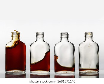 Four glass bottles in a row with different amount of brown color beverage in each, that churning and spills out.