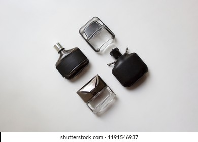 Four glass perfume bottles isolated on white background from a high angle view