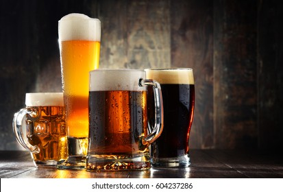 Four glasses of beer on wooden background.