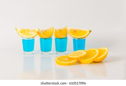 Four glasses of blue kamikaze, glamorous drink, mixed drink poured into shot glasses, party set