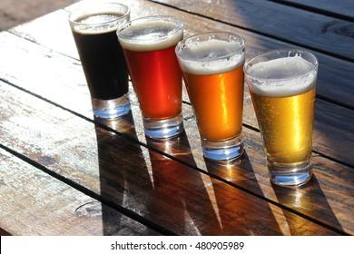 Quatre verres de bières artisanales sur une table en bois lors d'une dégustation