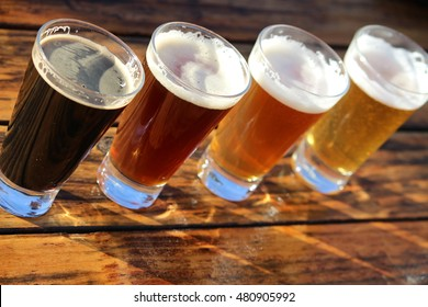 Four glasses of different craft beers on a wooden table during a tasting