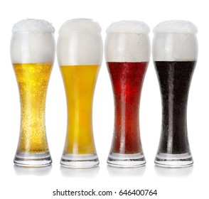 Four glasses of different fresh foamy beer on white background