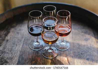 The four glasses with four different kinds of Porto wine placed on the wine barrel.