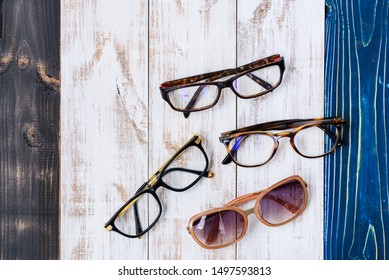 four glasses on the retro wooden background for sale. Sunglasses and eye glasses lay down on timber flat lay. Vision accessory.