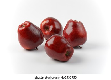 four glossy red apples on off-white background
