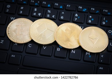 Four golden crypto currency coins - Bitcoin, NEO, Monero, Ethereum on black keyboard of laptop