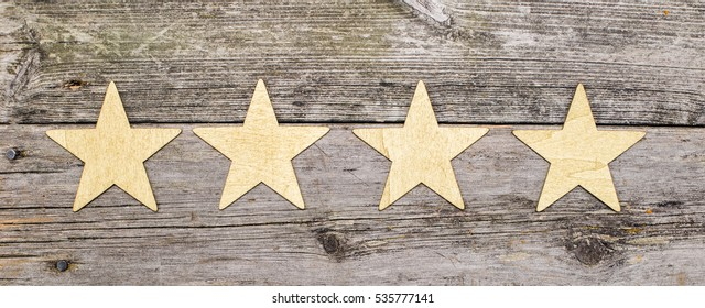 four golden stars in a row on wooden background header