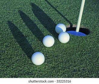 four golf balls heading toward cup on green