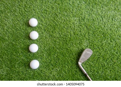 Four golf balls are on green grass for practicing.