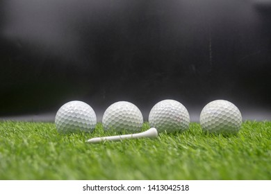 Four golf balls are on green grass.