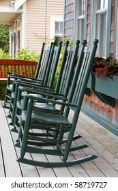 Four green wooden rocking chairs on a porch with partial wood swing