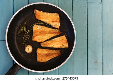 Four grilled smoked haddock fillets in cooking pan with rosemary brunch and garlic on turquoise background