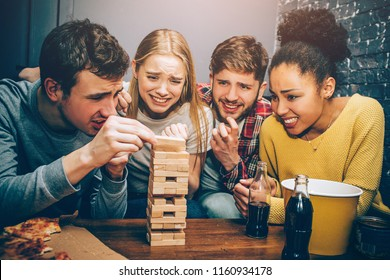 Four groupmates playing game. The game is intensive and hard. Seems like this pieces of towel will fall down very soon because of the guy on the left.