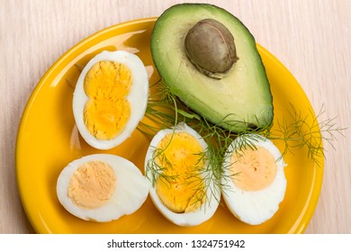 Four halves of boiled eggs and avocado on a yellow plate. Egg with two yolks
