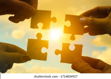 Four hands of businessmen assemble pieces of a puzzle into a single whole against the backdrop of the sunset, business concept idea, partnership, teamwork, cooperation, creative