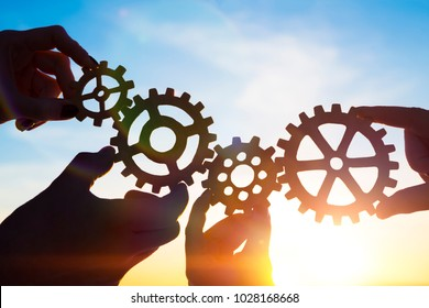 Four hands of businessmen collect gear from the gears of the details of puzzles. against the background of sunlight. The concept of a business idea. Teamwork. strategy. cooperation