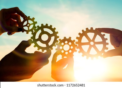 Four hands of businessmen collect gear from the gears of the details of puzzles. against the sunset. The concept of a business idea. Teamwork, strategy, cooperation, innovation.