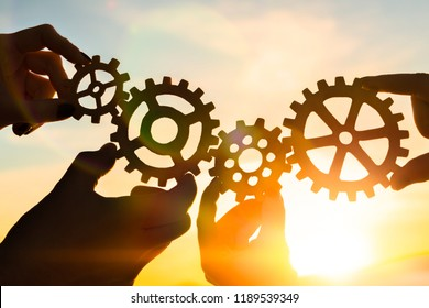Four hands of businessmen collect gear from the gears of the details of puzzles. against the backdrop of dramatic sunlight. The concept of a business idea. Teamwork, strategy, cooperation, creativity