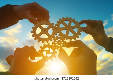 Four hands of businessmen collect gear from the gears of the details of puzzles. against the background of sunlight. The concept of a business idea. Teamwork. strategy. Collaboration, partnership