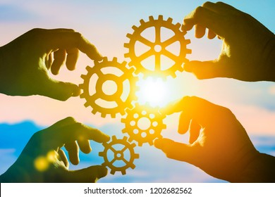Four hands of businessmen collect puzzles from the gear in one mechanism. Collaboration, teamwork, strategy, creativity, innovation. The idea of a business concept.