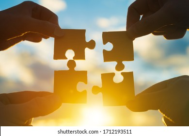 Four hands of businessmen connect puzzle pieces into a single unit on a sunset background. Business concept idea, teamwork, cooperation, partnership, creative