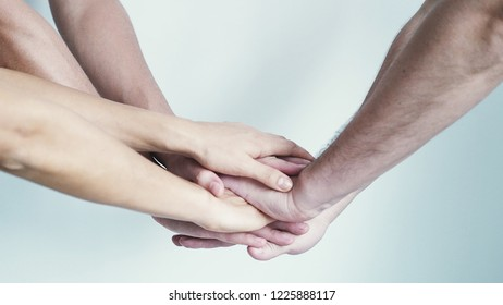 Four hands getting together on a white background.
