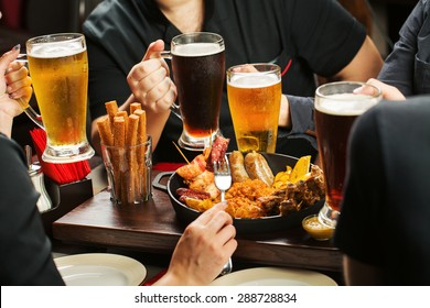 four Hands holding beer glasses drinking together in the pub