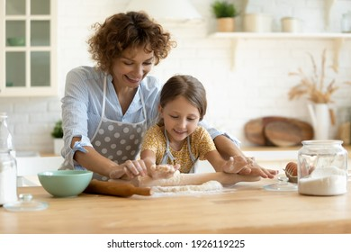 In four hands. Loving family of single mother small daughter child baking cake pastries cooking pie on dessert. Happy young mom bake sweet cookies with little kid roll dough at kitchen table using pin