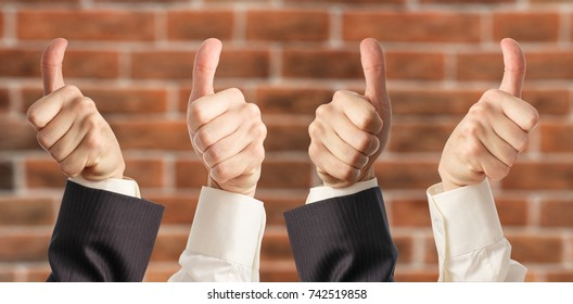 Four hands show thumbs up sign in closeup