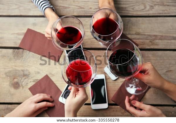 Cuatro manos con teléfonos inteligentes sosteniendo gafas con vino tinto, sobre fondo de mesa de madera