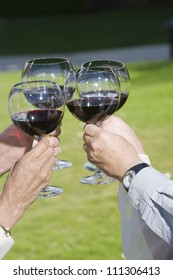 Four hands toasting wine glasses