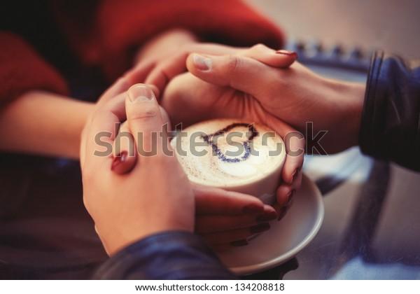 Четыре руки обернутые вокруг чашечки кофе с рисунком сердца