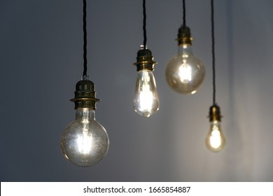 Four hanging light bulbs in the dark room