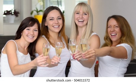 Four happy attractive girlfriends celebrating with flutes of champagne as they toast a special occasion or see in the New Year