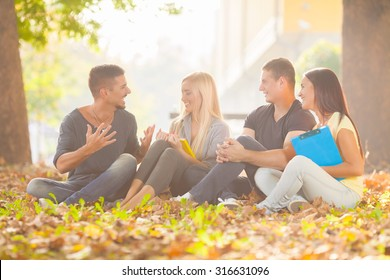Four happy college students relaxing in a university campus
