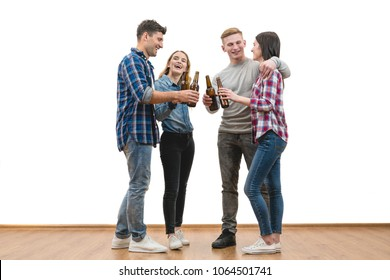 The four happy friends drink a beer on a white wall background