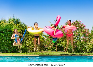 Four happy friends jumping into the swimming pool