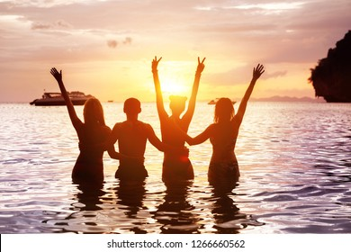 Four happy friends are meeting sunset at sea beach standing in water and hugging with raised arms