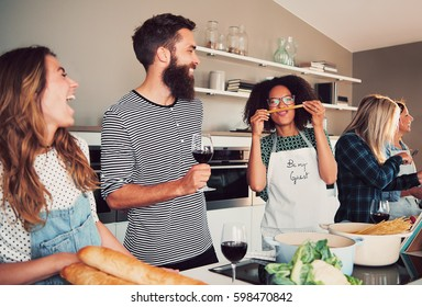 Four happy friends playing with food while cooking for dinner or a culinary class indoors