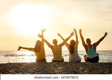 Four happy friends seats on the beach and having fun with raised arms